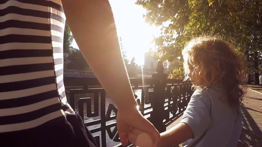 SLOW MOTION.  Little boy and girl 11 years walking in a city park along the river. Children hold hands and through Handshake seen sunlight. The camera moves for the kids.