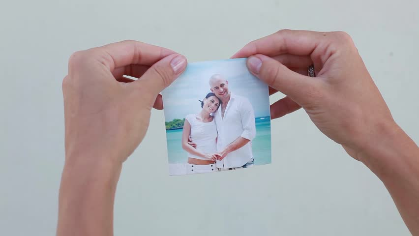 woman tearing a photo of a couple. Divorce concept