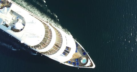 Aerial view of luxury medium cruise ship sailing from port on sunrise through the bay