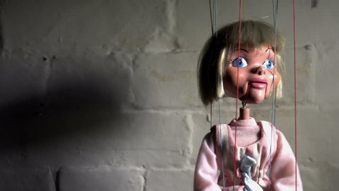 Creepy old puppet swinging on strings, blank space to one side