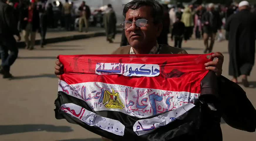 CAIRO - CIRCA JAN 2011: Man waves anti-mubarak flag, Tahrir Square, circa January 2011, Cairo, Egypt. Tahrir Square was the focal point of the 2011 Egyptian Revolution where demonstrations grew to 250,000 plus people by day 6, January 31, 2011.
