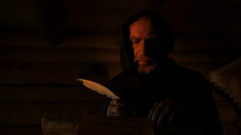KIEV/UKRAINE - JUL 14 2015: Dark Room in an old log hut of the 11th century. Candlelight. Old man, monk, chronicler, dressed in black robe, in the hood. Nestor the Chronicler. He writes with a quill