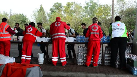 Volunteers from Red cross distributing help for refugees in Hungary - Austria border. These refugees are from Syria, Iraq and Afghanistan and they will go to Germany. October 6, Hegyeshalom, Hungary