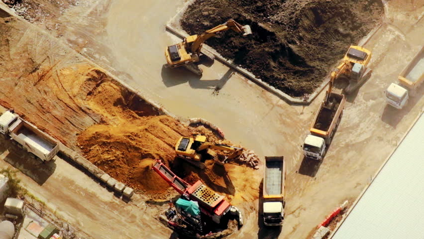 Excavators and tipper tracks working at construction. Hong Kong. Video form aerial view point