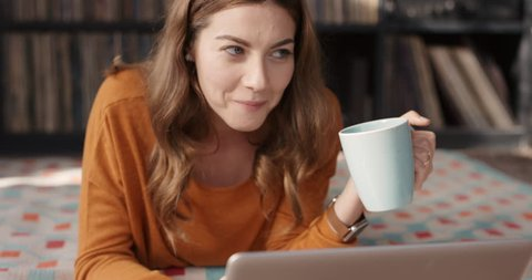 Cool happy woman laughing at funny streaming movie on laptop at home drinking coffee having fun alone