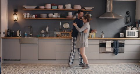 Happy young couple newly wed dancing listening to music in kitchen wearing pajamas coffee morning at home in love having fun