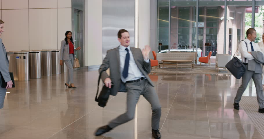 Crazy happy businessman dancing in corporate lobby wearing suit celebrating achievement #12322181