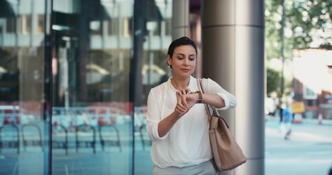 Smart Middle Eastern businesswoman using smartwatch touchscreen commuting to work entering glass corporate building smiling
