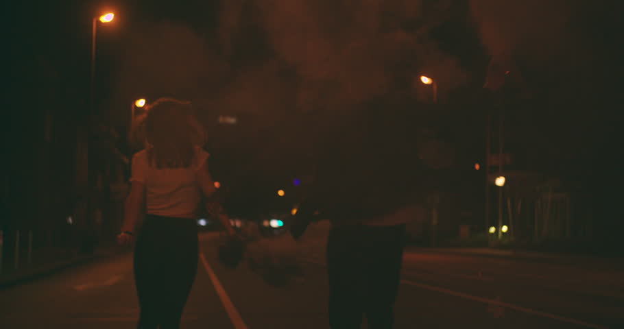 Teenage guy and girl running down a late night city street carrying smoke flares under the street lights in Slow Motion