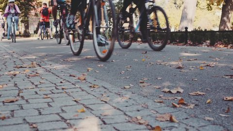 Steadicam shot of group of cyclists lower bodies peddling fast on a bicycle road. 4K Ultra HD, UHD. Healthy lifestyle in the city. Sports and active life. Close up bicycle wheels. Unrecognizable.