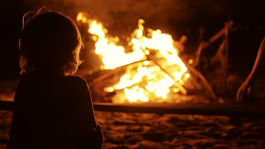 Silhouette of child in front of the bonfire on beach party in the dark. Spending time at campfire making barbecue at night. Slow motion. Vietnam