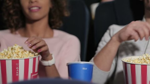Couple in cinema theater watching a movie, they eating popcorn. Cinema, entertainment and people concept - happy friends watching movie in theater. Couple and other people eating popcorn and drinking