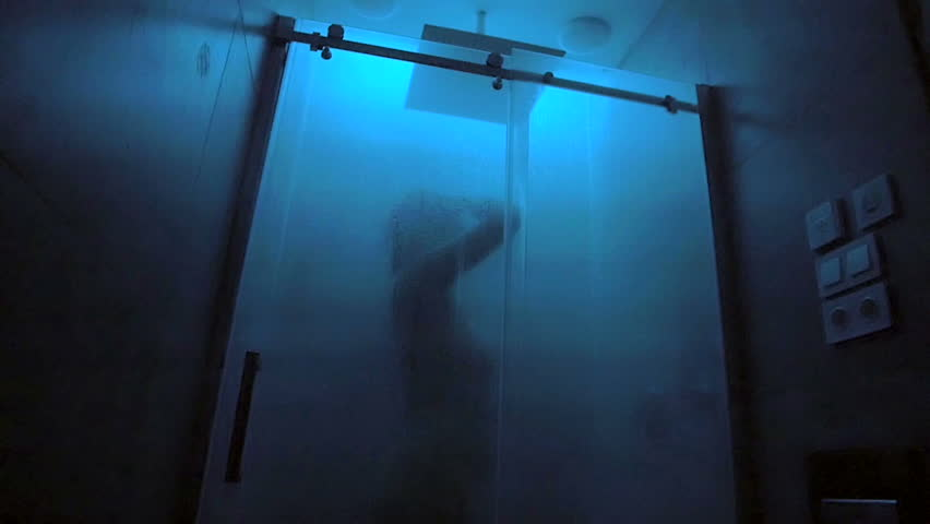 Naked woman taking a shower behind glass screen in a bathroom / slowmation  / camera moving forwards