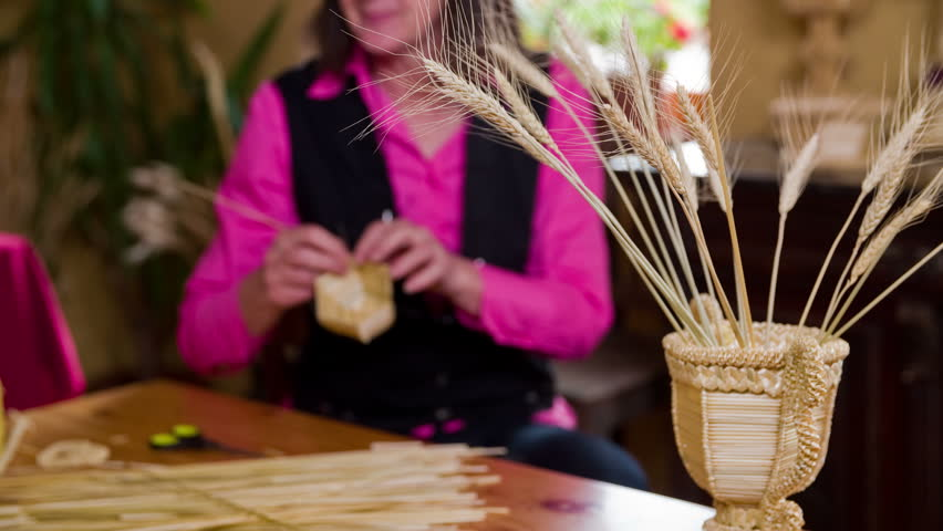 Flower vase from knitted dried straws on table 4K. Traditional hand-made vase decoration for flowers in front of woman crafting a new product from wheat straws.