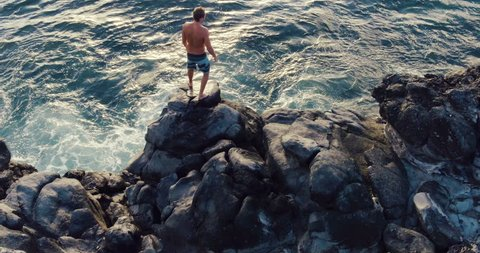 Aerial Flight Over Young Man Jumping Back Flip Off Ocean Sea Cliff into Sunset. Extreme Outdoor Summer Sports.