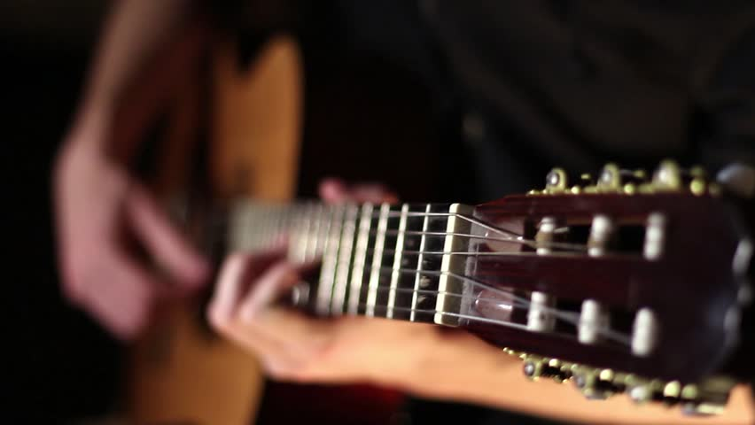 Acoustic, classic, wooden guitar. Brown guitar. Musician plays work. Measured play flamenco. Black background. Fast guitar solo. Six strings. Pluck the strings. Playing with your fingers. Rock'n'roll.