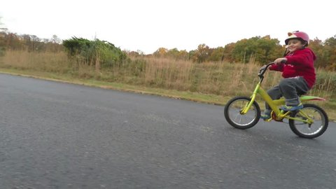Boy Riding a bicycle on a country Road During Fall Season. Boy Wearing Bright Red And Yellow Contrasting Colors of Fall.