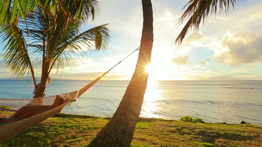 Romantic young couple relaxing in tropical hammock at sunset. Summer Luxury Vacation