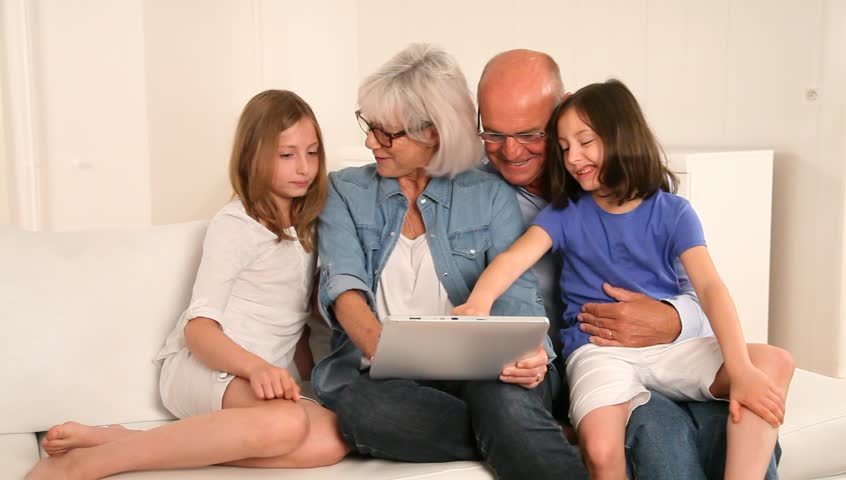 Senior people with grandkids using electronic tablet
