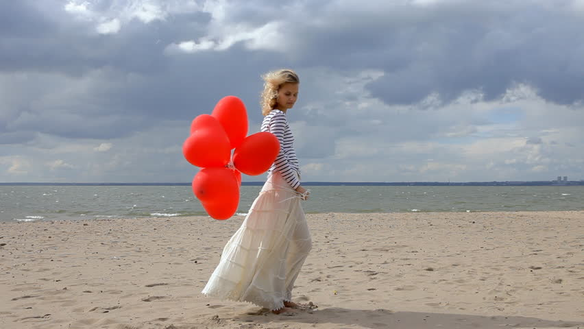 Young woman with red heart balloons standing on the beach in cloudy day at sea | Shutterstock HD Video #12557321