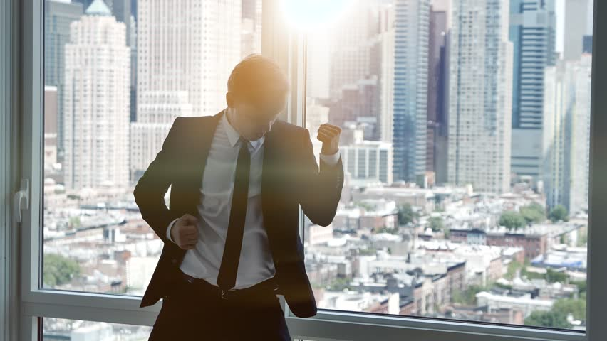 Young successful business man dancing in modern office. cityscape skyline background | Shutterstock HD Video #12600524