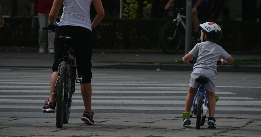 OPOLE/POLAND - AUG 22 2015: Woman and the kid in helmet ride on the bicycles across the crosswalk. Other bicyclers and pedestrians move on the crosswalk. Car moves by paved auto road. Summer August