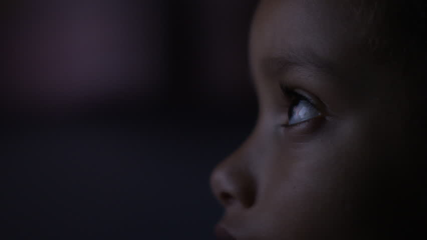 4K Close up of child's eyes watching a colourful screen in the dark, in slow motion