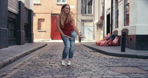Contemporary street dancer woman happy funky urban dancing freestyle in the city