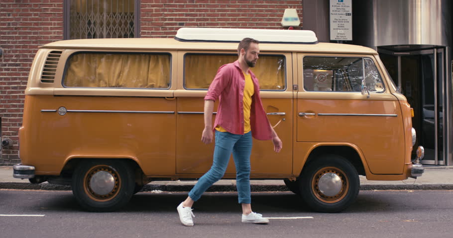 Contemporary happy caucasian man funky street dancer vintage camper van dancing freestyle in the city hippie van