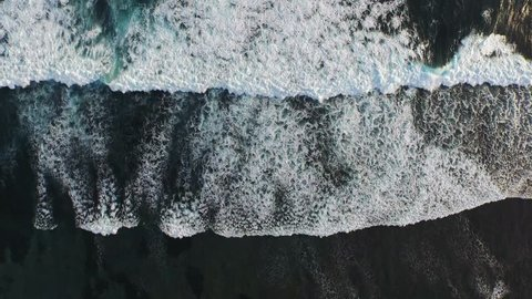 A beautiful aerial view of the oceanic waves breaking over a shallow reef (drone footage shot in Bali, Indonesia)