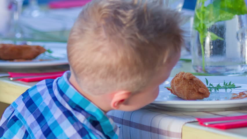 Young boy is playing with his food in a restaurant. Close-up shot. He looks very happy. | Shutterstock HD Video #12718751