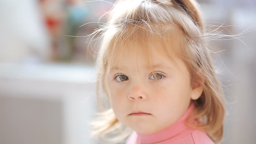 Blue-eyed blonde little girl looking bored and serious HD