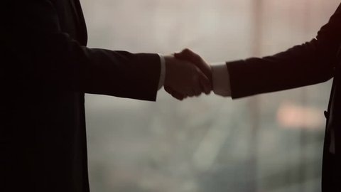 Close up of two businessmen shaking hands in a modern office. Silhouette shot.