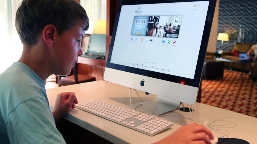 BOSTON - SEP 6, 2014: Boy works with computer Apple. Through innovative technology and aesthetic design, Apple acquired unique reputation comparable to cult in consumer electronics industry | Shutterstock HD Video #12741995