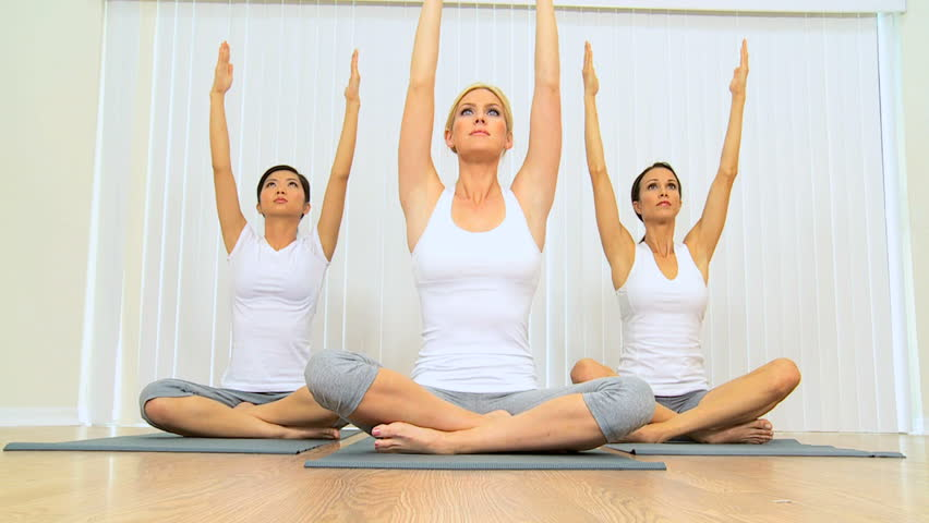 Group of females practicing yoga at health studio