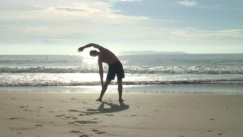 Man doing yoga on the beach at sunrise.