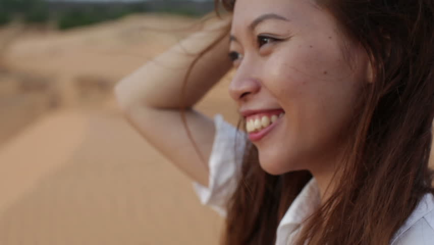 Asian woman smile outdoor desert wind blowing hair, profile side view close up face of young happy girl
