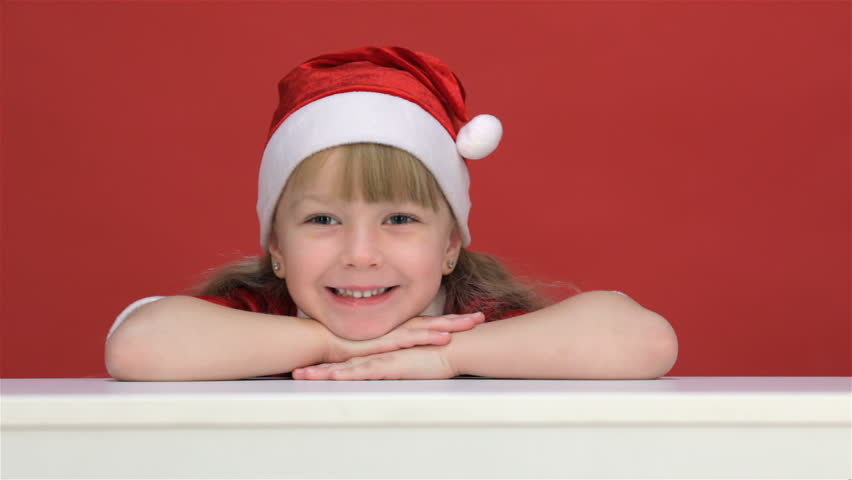 Kid girl in a red suit and Santa hat smiling resting his chin on his hands.  Kid girl in Santa hat posing in a studio. Isolated on a white background. b5be0a80f416