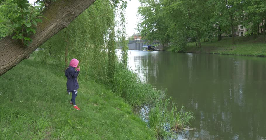 Child girl is on the the lakeside. She is surrounded by green thees and grass, dressed in violet raincoat. Water is silty. She is holding a black fishing rod and tries to catch a fish | Shutterstock HD Video #12763541