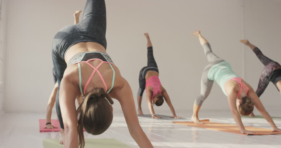 Yoga class multi racial group of women exercising healthy lifestyle in fitness studio yoga warrior poses | Shutterstock HD Video #12794927