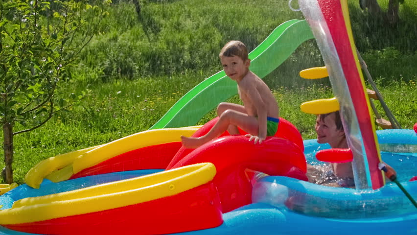 Kid sliding down on inflatable water pool. Two boys having fun in air pool with water, a slide in between. Pool on grass.