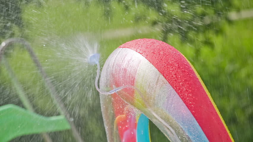 Water sprinkler on inflatable kid pool. Water sprinkling all around from inflated pool. Close up view of top bow over small kids pool.