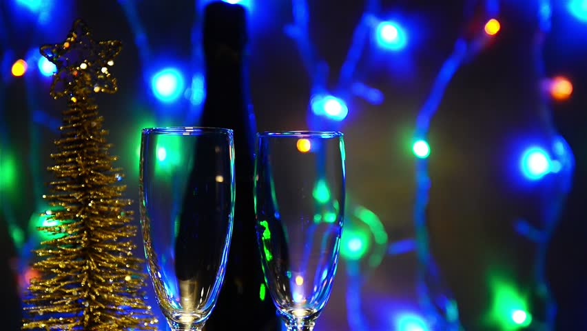 Champagne is poured into glasses on a background of garlands. new year theme video full HD 1920 * 1080   Shutterstock HD Video #12808541