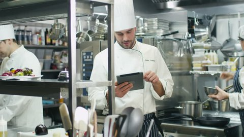 Professional chef in a commercial kitchen in a restaurant or hotel is using a tablet computer. Shot on RED Cinema Camera in 4K (UHD).