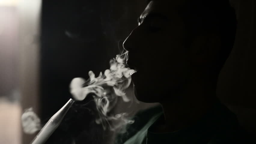 Young man smokes hookah and lets out smoke rings in a dark room close up.