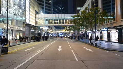 HONG KONG - FEBRUARY 01, 2015: POV move at empty road after protest action, police officers groups, several people, deserted city street at late evening time. Driveway was closed for public action.