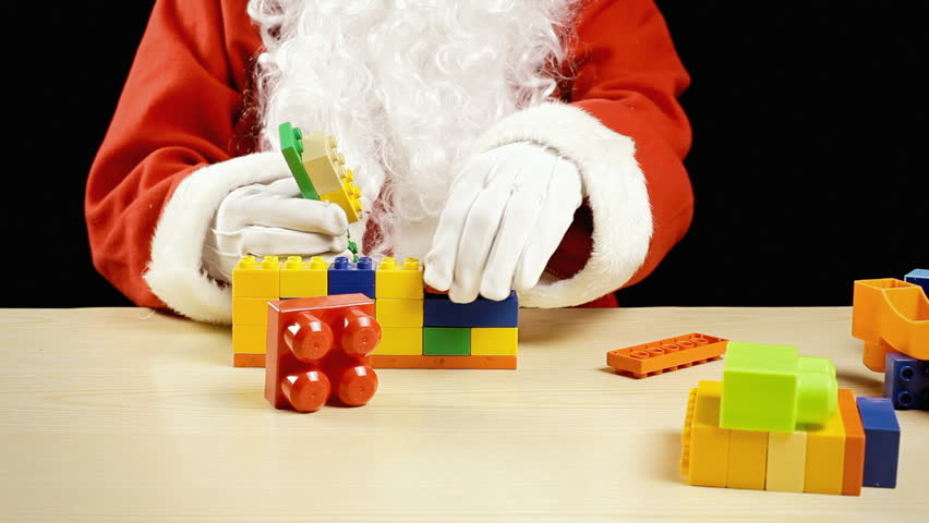 Santa Claus playing with building blocks (construction set toy). Timelapse.
