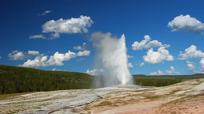 Old Faithful Geyser erupts on a beautiful evening in Yellowstone National Park - USA