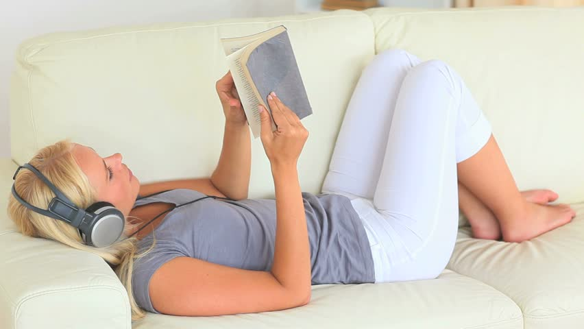 Woman lying on a sofa in the living room while listening to music with headphones and reading a book
