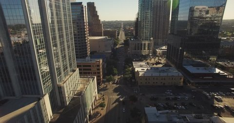 The camera flies south over Congress Avenue in Austin, Texas at a high altitude, showcasing Lady Bird Lake in the distance as well as the sun peeking through the downtown skyline.